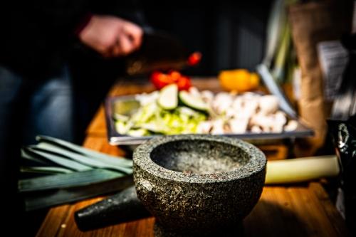 Ein Mörser ist scharf im Vordergrund, dahinter liegen verschiedene Gemüsearten geschnitten ein einer Schale und dahinter werden Paprikas geschnitten