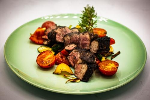 Geschnittenes Steak mit Gemüse (Tomaten, Paprika und Lauch) auf einem Teller
