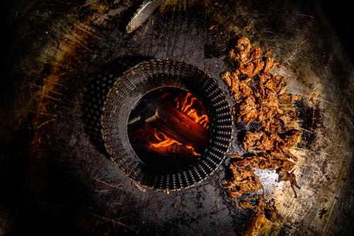 Grilltonne mit Blick auf das gühende Holz in der Tonne, auf der Tonne liegt Pulled Pork