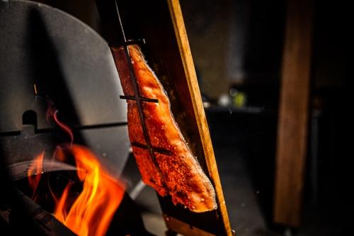 Lachs von der Planke über dem offenen Grill wo Flammen herauskommen