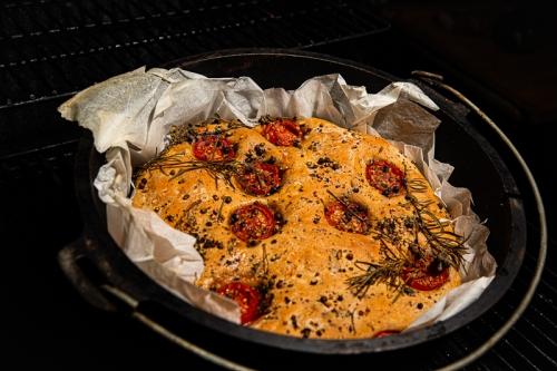 Focaccia mit Tomaten und Oliven im Teuertopf und garniert mit Rosmarin